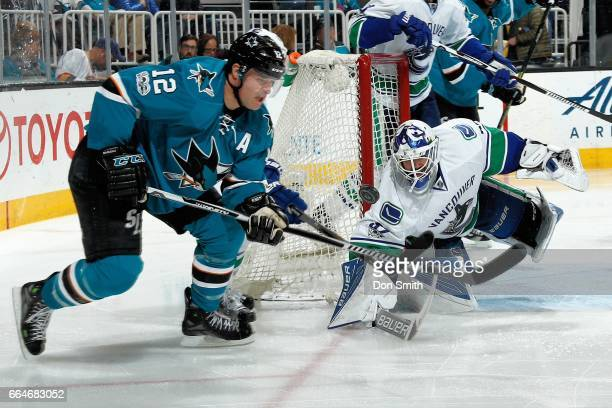 Patrick Marleau of the San Jose Sharks follows the puck as Richard Bachman of the Vancouver Canucks goes to block during a NHL game at SAP Center at...