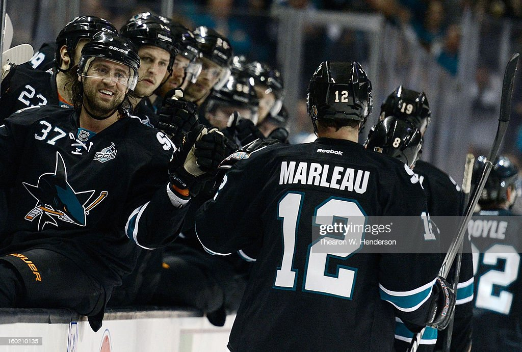 Patrick Marleau #12 of the San Jose Sharks is congratulated by teammate Adam Burish #37 after Marleau scored his 9th goal of the season against the Vancouver Canucks in the second period of their game at HP Pavilion on January 27, 2013 in San Jose, California.