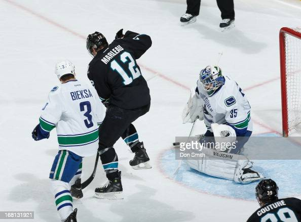 Patrick Marleau of the San Jose Sharks looks for a rebound against Kevin Bieksa and Cory Schneider of the Vancouver Canucks in Game One of the...