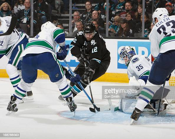 Patrick Marleau of the San Jose Sharks looks for a rebound against Cory Schneider Alexander Edler and Alexandre Burrows of the Vancouver Canucks in...