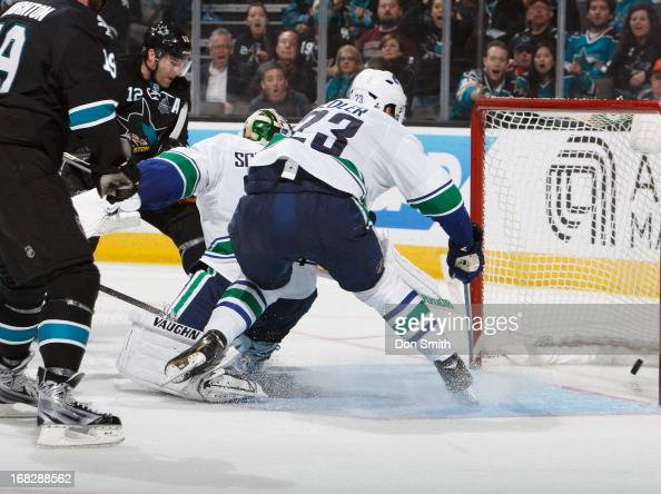 Patrick Marleau of the San Jose Sharks scores the gamewinning goal in overtime against Cory Schneider and Alexander Edler of the Vancouver Canucks in...