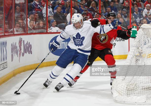 Patrick Marleau of the Toronto Maple Leafs fends off JeanGabriel Pageau of the Ottawa Senators as he stickhandles the puck behind the net at Canadian...