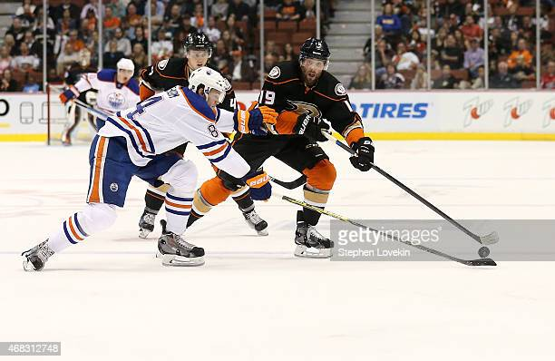 Patrick Maroon of the Anaheim Ducks and Oscar Klefbom of the Edmonton Oilers reach for the puck at Honda Center on April 1 2015 in Anaheim California...