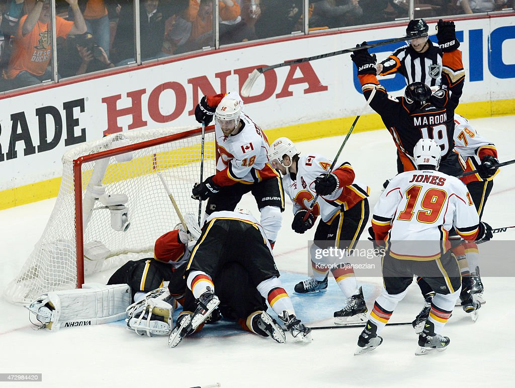 Patrick Maroon #19 of the Anaheim Ducks celebrates teammate Corey Perry's #10 game-winning goal in overtime against goalie Karri Ramo #31 Matt Stajan #18 and Kris Russell #4 in Game Five of the Western Conference Semifinals during the 2015 Stanley Cup Playoffs at Honda Center on May 10, 2015 in Anaheim, California.