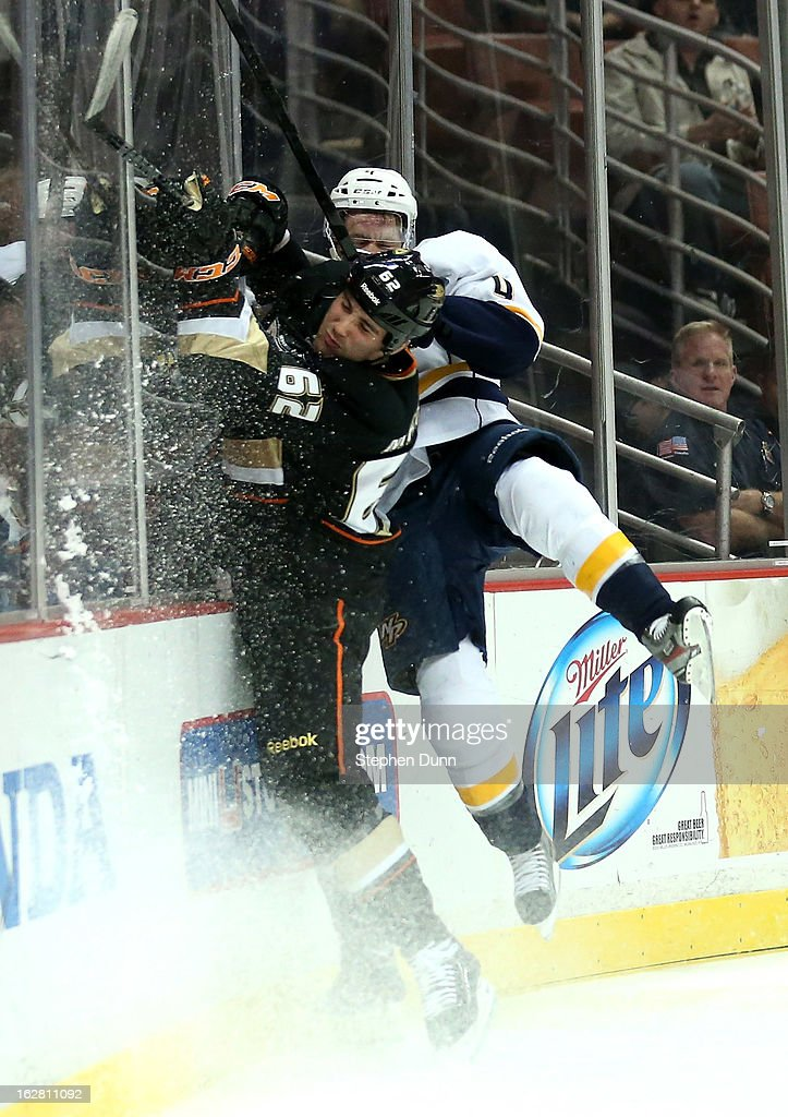 Patrick Maroon #62 of the Anaheim Ducks collides with the boards and <a gi-track='captionPersonalityLinkClicked' href=/galleries/search?phrase=Ryan+Ellis+-+Ice+Hockey+Player&family=editorial&specificpeople=15459795 ng-click='$event.stopPropagation()'>Ryan Ellis</a> #4 of the Nashville Predators at Honda Center on February 27, 2013 in Anaheim, California. The Ducks won 5-1.