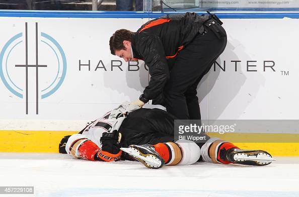 Patrick Maroon of the Anaheim Ducks is helped by a trainer after being injured against the Buffalo Sabres on October 13 2014 at the First Niagara...