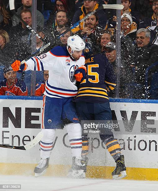 Patrick Maroon of the Edmonton Oilers checks Brendan Guhle of the Buffalo Sabres during an NHL game at the KeyBank Center on December 6 2016 in...