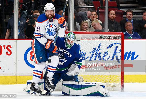 Patrick Maroon of the Edmonton Oilers takes a puck to the knee in front of Jacob Markstrom of the Vancouver Canucks during their NHL game at Rogers...