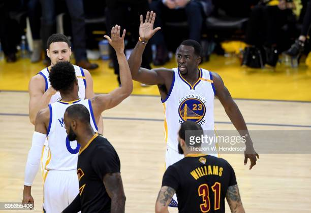 Patrick McCaw Klay Thompson and Draymond Green of the Golden State Warriors react to a play against the Cleveland Cavaliers in Game 5 of the 2017 NBA...