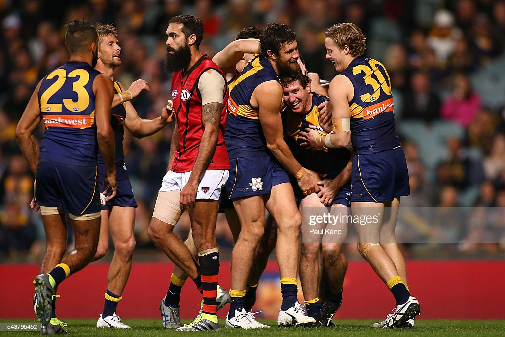 Patrick McGinnity of the Eagles is congratulated by team mates after kicking a goal as Courtenay Dempsey of the Bombers walks past during the round 15 AFL match between the West Coast Eagles and the Essendon Bombers at Domain Stadium on June 30, 2016 in Perth, Australia.