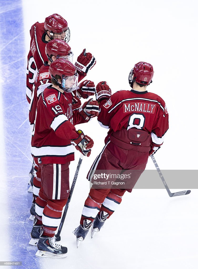 Patrick McNally of the Harvard Crimson greets his teammates Sean Malone Jimmy Vesey and Brian Hart before NCAA hockey action against the Boston...