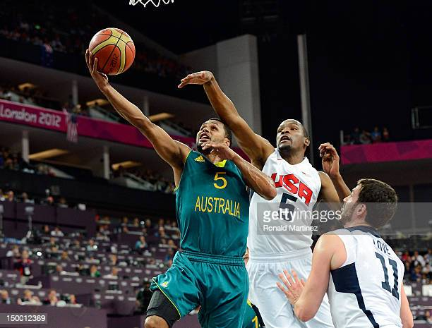 Patrick Mills of Australia lays the ball up in front of Kevin Durant and Kevin Love of United States in the first half during the Men's Basketball...