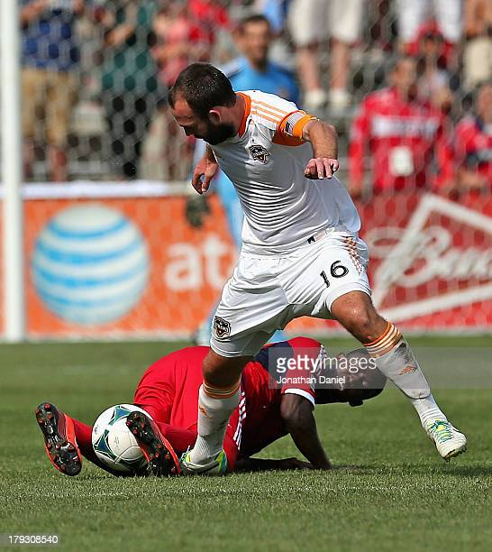 Patrick Nyarko of the Chicago Fire traps the ball between his legs under Adam Moffat of the Houston Dynamo during an MLS match at Toyota Park on...