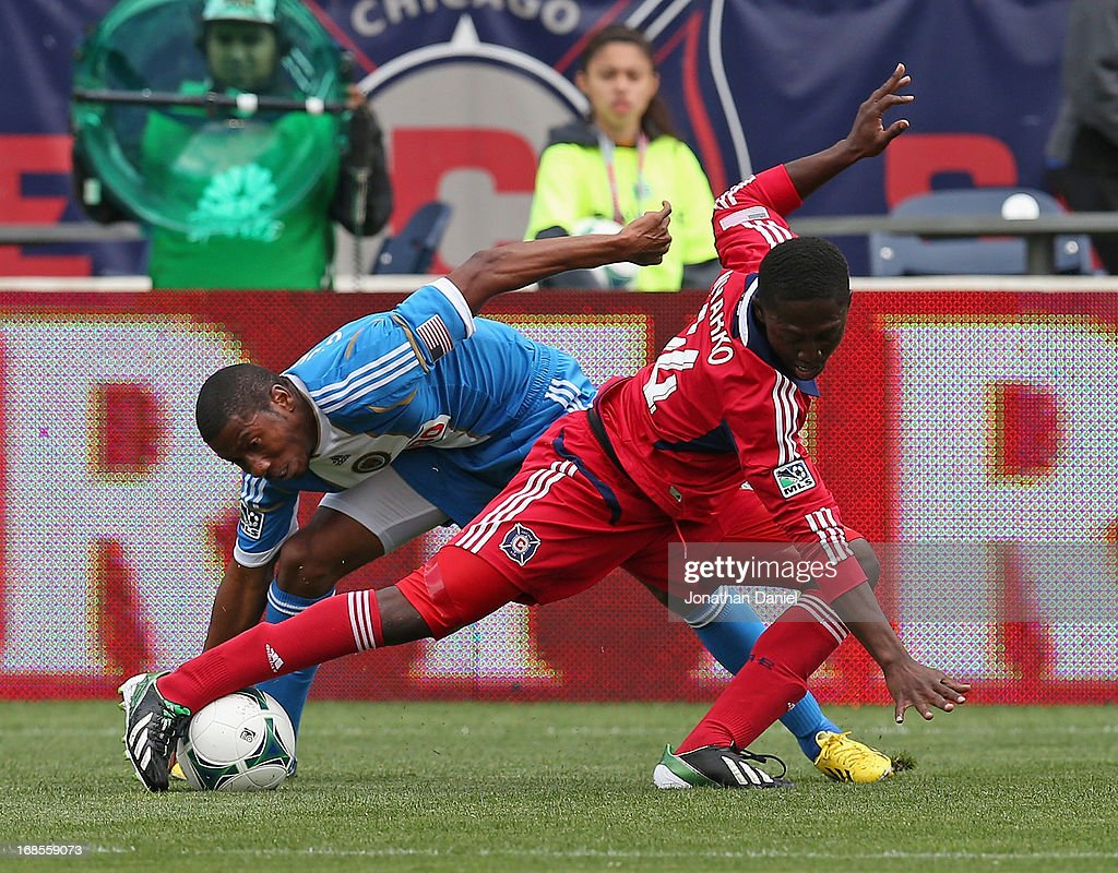 Patrick Nyarko #14 of the Chicago Fire tries to control the ball under pressure from Raymon Gaddis #28 of the Philadelphia Union during an MLS match at Toyota Park on May 11, 2013 in Bridgeview, Illinois.