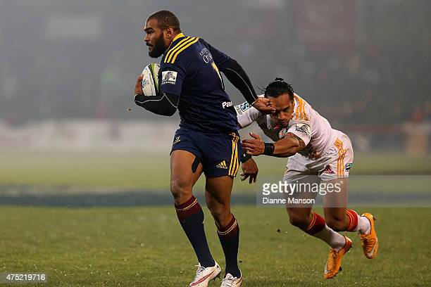Patrick Osborne of the Highlanders breaks the tackle of Hosea Gear of the Chiefs during the round 16 Super Rugby match between the Highlanders and...