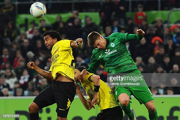 Patrick Owomoyela of Dortmund and Sebastian Proedl of Bremen jump for a header during the Stadtwerke Duesseldorf Wintercup 2012 third place match...