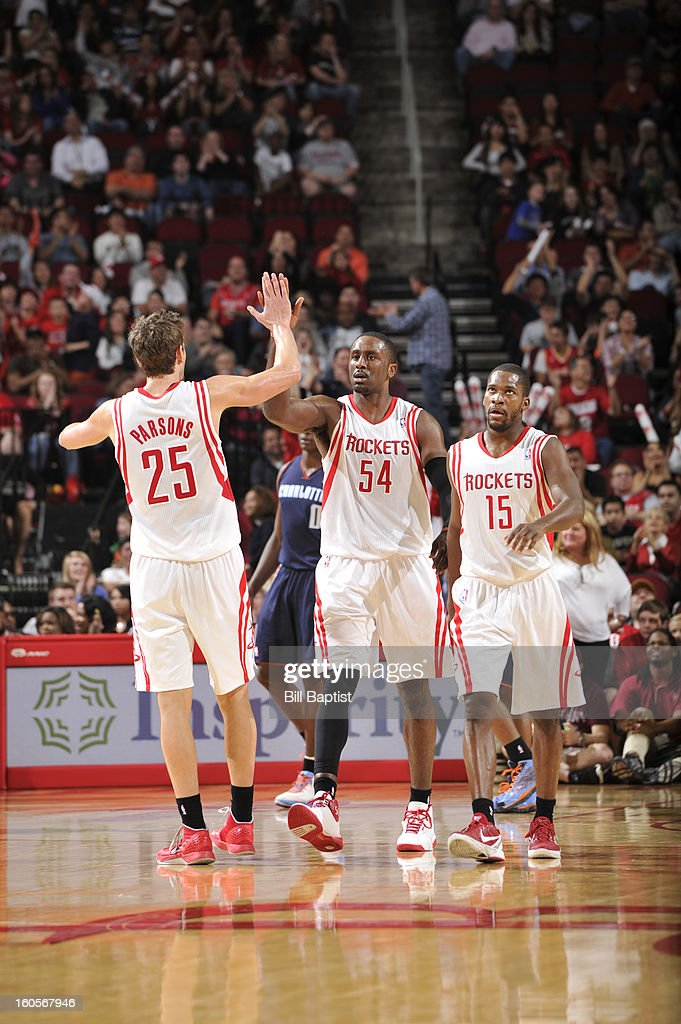 Patrick Patterson #54, Chandler Parsons #25 and Toney Douglas #15 of the Houston Rockets celebrate a win against the Charlotte Bobcats on February 2, 2013 at the Toyota Center in Houston, Texas.