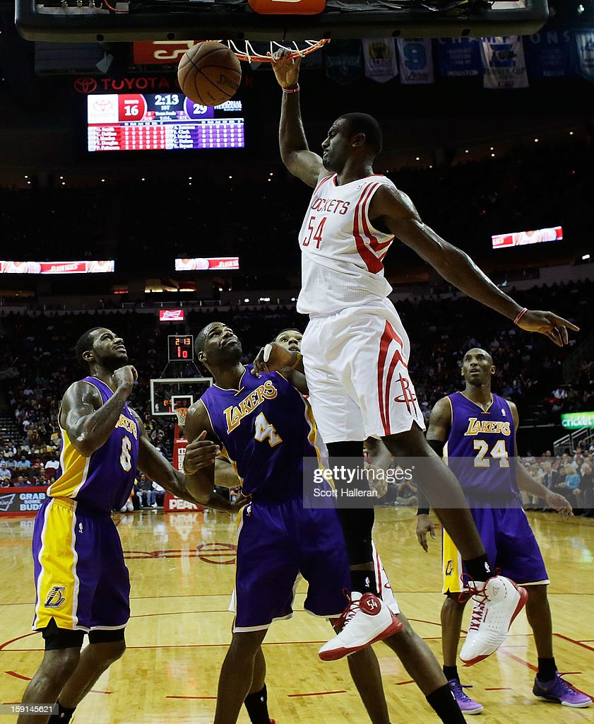 Patrick Patterson #54 of the Houston Rockets goes up for a dunk against Antawn Jamison #4 and Earl Clark #6 of the Los Angeles Lakers at Toyota Center on January 8, 2013 in Houston, Texas.