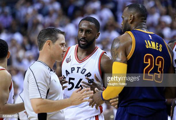 Patrick Patterson of the Toronto Raptors and LeBron James of the Cleveland Cavaliers react with an official after a foul in the second half in game...