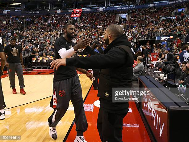 Patrick Patterson of the Toronto Raptors greets Drake during the game against the Golden State Warriors December 5 2015 at Air Canada Centre in...