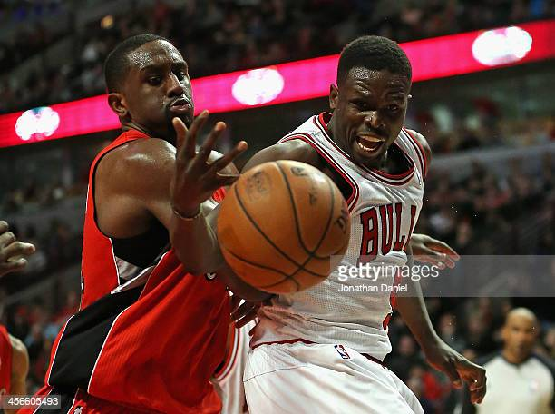 Patrick Patterson of the Toronto Raptors knocks the ball away from Loul Deng of the Chicago Bulls at the United Center on December 14 2013 in Chicago...