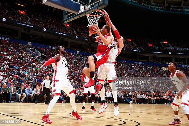 Patrick Patterson of the Toronto Raptors looks on as teammate Jonas Valanciunas grabs Blake Griffin of the Los Angeles Clippers during their NBA...