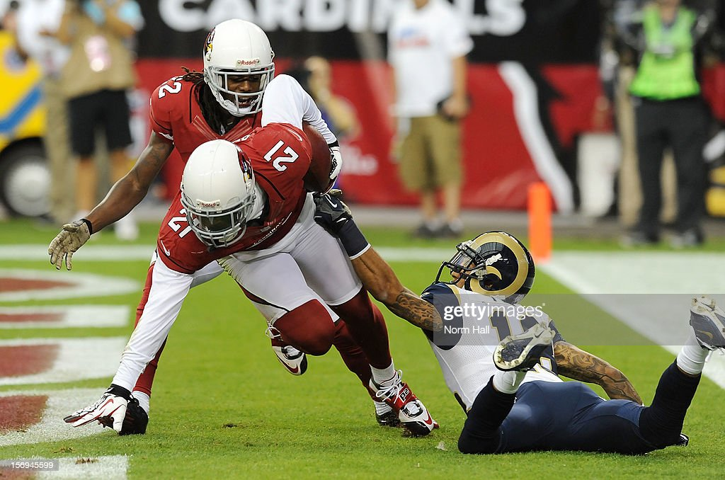 Patrick Peterson of the Arizona Cardinals intercepts the ball in the endzone as Austin Pettis of the St Louis Rams attempts to strip the ball at...