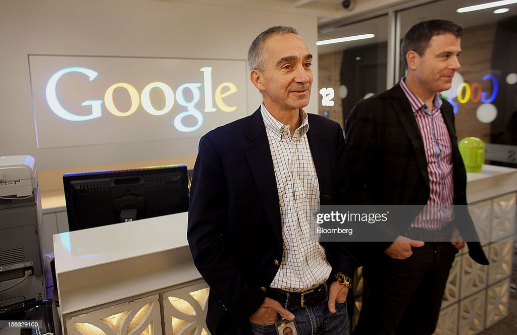 Patrick Pichette, chief financial officer of Google Inc., left, and Chris O'Neil, managing director of Google Inc. Canada, stand at the front desk during a media tour for the grand opening of Google Inc.'s new office in Toronto, Ontario, Canada, on Tuesday, Nov. 13, 2012. The office space encompasses five color-coded floors and features amenities such as a pool table, video games, mini-golf putting greens and a camping lounge where employees can hold meetings in a tent. Photographer: Brett Gunlock/Bloomberg via Getty Images