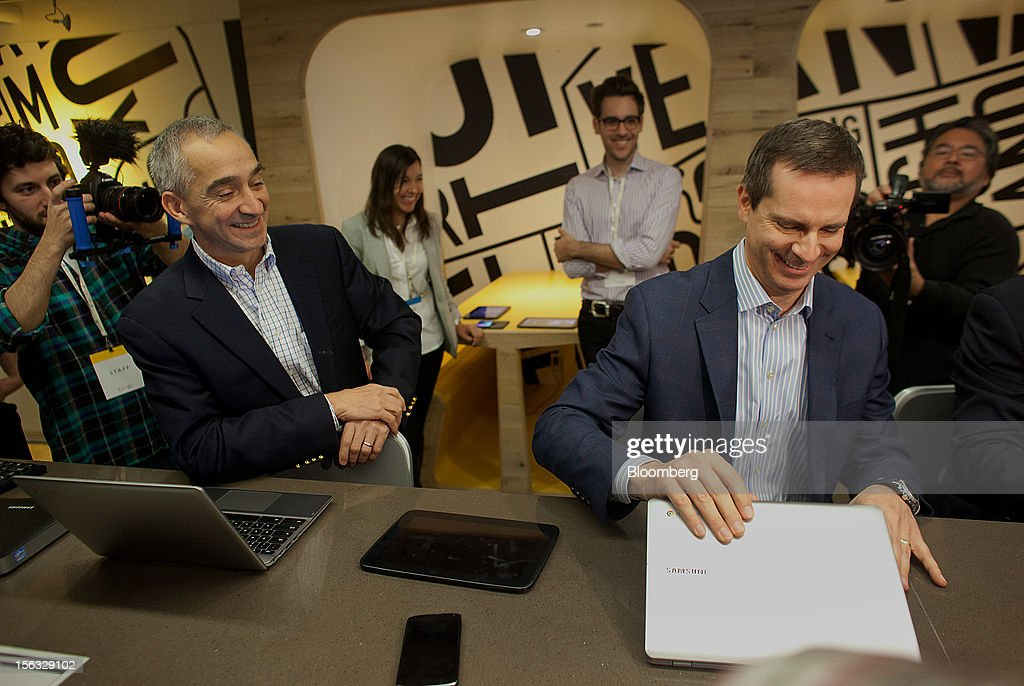 Patrick Pichette, chief financial officer of Google Inc., left, and Dalton McGuinty, Ontario's premier, look at new products during a media tour for the grand opening of Google Inc.'s new office in Toronto, Ontario, Canada, on Tuesday, Nov. 13, 2012. The office space encompasses five color-coded floors and features amenities such as a pool table, video games, mini-golf putting greens and a camping lounge where employees can hold meetings in a tent. Photographer: Brett Gunlock/Bloomberg via Getty Images