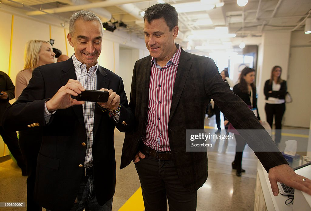 Patrick Pichette, chief financial officer of Google Inc., left, shows Chris O'Neil, managing director of Google Inc. Canada, a photo on his phone during a media tour for the grand opening of Google Inc.'s new office in Toronto, Ontario, Canada, on Tuesday, Nov. 13, 2012. The office space encompasses five color-coded floors and features amenities such as a pool table, video games, mini-golf putting greens and a camping lounge where employees can hold meetings in a tent. Photographer: Brett Gunlock/Bloomberg via Getty Images
