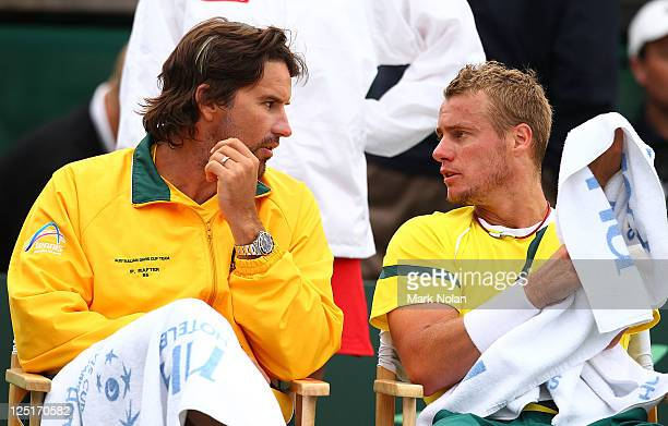 Patrick Rafter and Lleyton Hewitt of Australia chat during a break in their Davis Cup World Group Playoff Tie match against Roger Federer of...