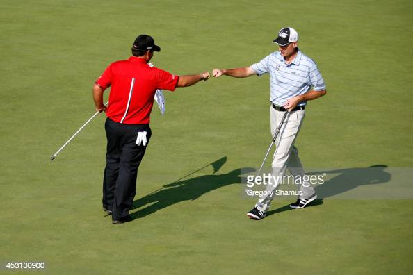 Patrick Reed and Jim Furyk celebrate after Reed's eagle on the 17th green during the final round of the World Golf ChampionshipsBridgestone...