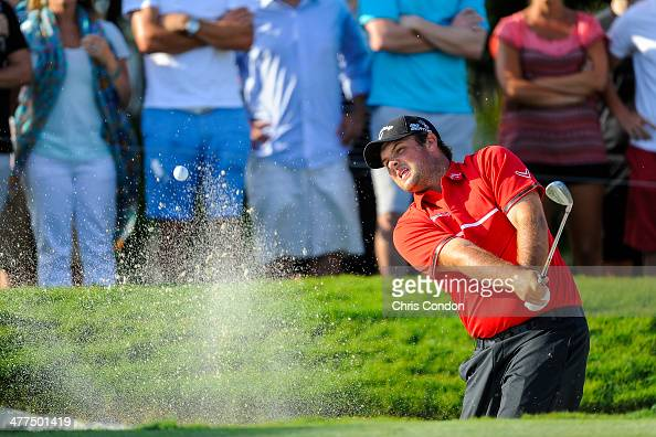 Patrick Reed chips his second shot out of a bunker on the 13th hole during the final round of the World Golf ChampionshipsCadillac Championship at...