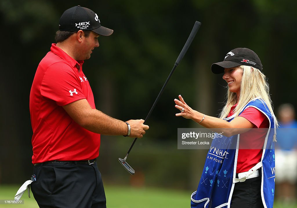 Patrick Reed hands his putter to his caddie and wife Justine Reed during the final round of the Wyndham Championship at Sedgefield Country Club on August 18, 2013 in Greensboro, North Carolina.