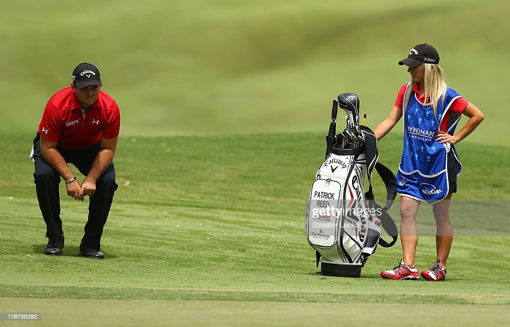 Patrick Reed lines up a putt with his caddie and wife Justine Reed during the final round of the Wyndham Championship at Sedgefield Country Club on August 18, 2013 in Greensboro, North Carolina.