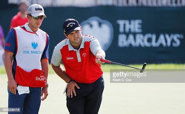 Patrick Reed lines up a putt with his caddie Kessler Karain on the 14th green during the second round of The Barclays in the PGA Tour FedExCup...