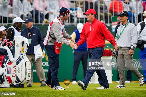 Patrick Reed of Team USA shakes hands with Jim 'Bones' Mackay as he walks to the 10th hole during the Sunday singles matches in the final round of...