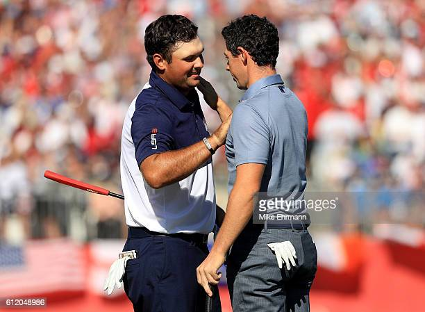 Patrick Reed of the United States shakes hands with Rory McIlroy of Europe after Reed won their match during singles matches of the 2016 Ryder Cup at...