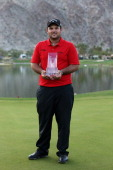 Patrick Reed poses with his trophy on the 18th green after winning the Humana Challenge in partnership with the Clinton Foundation on the Arnold...