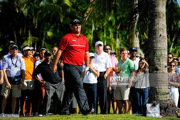 Patrick Reed reacts to his second shot on the tenth hole as businessman Donald Trump looks on at right during the final round of the World Golf...