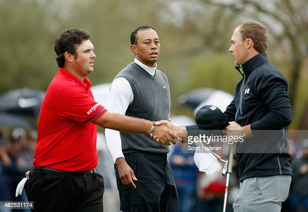 Patrick Reed shakes hands with Jordan Spieth on the ninth green as Tiger Woods looks on Woods shot an 11over par 82 during the second round of the...