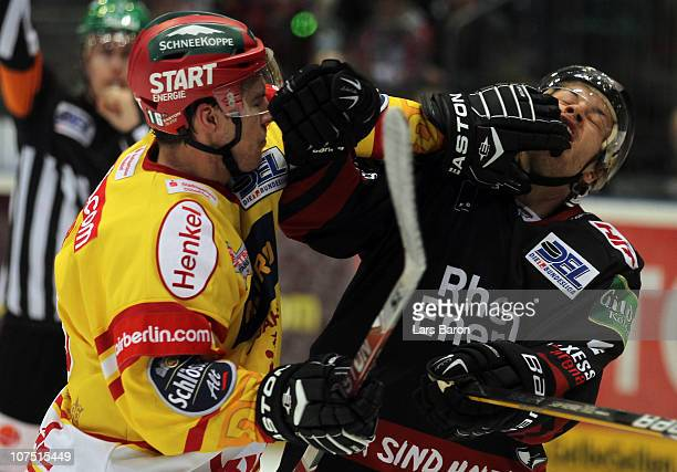 Patrick Reimer of Duesseldorf punshes Mike Card of Koeln during the DEL match between Koelner Haie and DEG Metro Stars at Lanxess Arena on December...