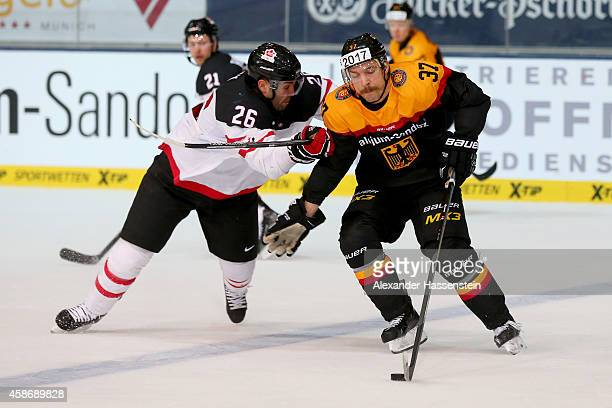 Patrick Reimer of Germany skates with Mathieu Roy of Canada during match 6 of the Deutschland Cup 2014 between Canada and Germany at Olympia Eishalle...