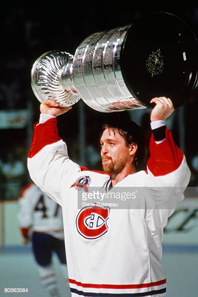 Patrick Roy of the Montreal Canadiens raises Stanley Cup in celebration after defeating the Los Angeles Kings in game at the Montreal Forum