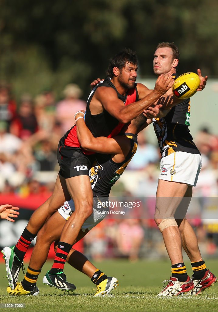 Patrick Ryder of the Bombers handballs whilst being tackled during the round two AFL NAB Cup match between the Essendon Bombers and the Richmond Tigers at Wangaratta Showgrounds on March 2, 2013 in Wangaratta, Australia.
