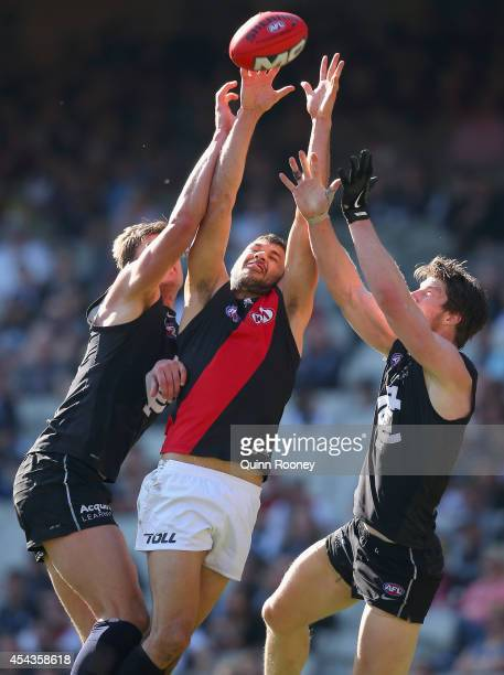 Patrick Ryder of the Bombers marks inbetween Cameron Wood and Sam Rowe of the Blues during the round 23 AFL match between the Carlton Blues and the...