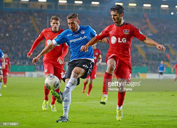 Patrick Schoenfeld of Bielefeld and Emir Spahic of Leverkusen fight for the ball during the DFB Cup match between Arminia Bielefeld and Bayer 04...