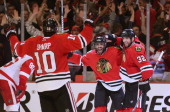 Patrick Sharp Johnny Oduya and Michal Rozsival of the Chicago Blackhawks celebrate Oduyas' third period goal against the Detroit Red Wings in Game...