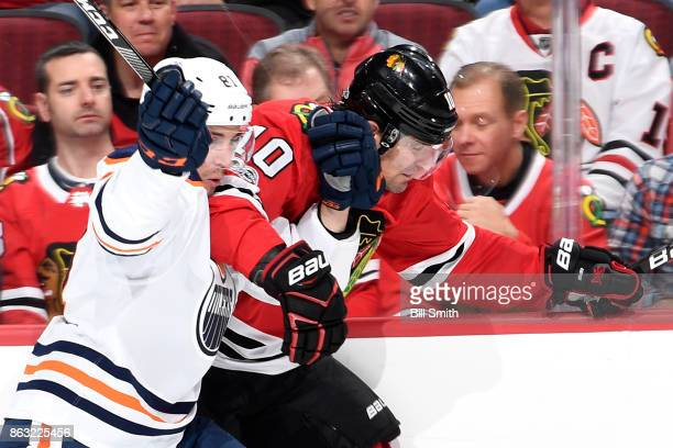 Patrick Sharp of the Chicago Blackhawks and Yohann Auvitu of the Edmonton Oilers get physical by the glass in the first period at the United Center...