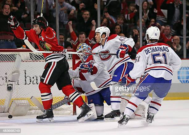 Patrick Sharp of the Chicago Blackhawks celebrates his gamewinning goal in overtime in front of Peter Budaj Mike Weaver and David Desharnais of the...